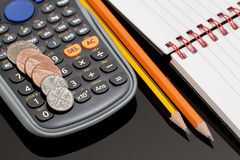 Account. Close up Image of a Notebook, Two Pencils, Coins and a Calculator on a Desktop with Black Glass Stock Photos