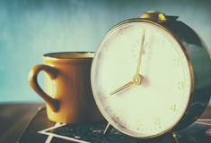 Close up image of old clock and cofee cup over wooden table. image is filtered with retro faded style royalty free stock photography