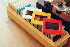 Close up image of old slides frames and old camera over wooden table Royalty Free Stock Photography