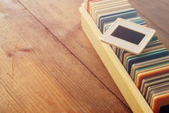 Close up image of old slides frames and old camera over wooden table Royalty Free Stock Photo