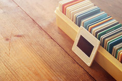 Close up image of old slides frames and old camera over wooden table Stock Photography