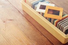 Close up image of old slides frames and old camera over wooden table Stock Image