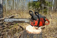 Old Used Chainsaw. A close up image of an old used chainsaw resting on a tree stump royalty free stock photography