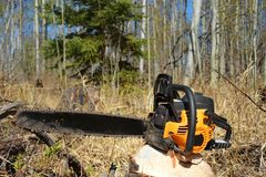 Old Used Chainsaw. A close up image of an old used chainsaw resting on a tree stump stock photos