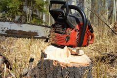 Old Used Chainsaw. A close up image of an old used chainsaw resting on a tree stump stock image