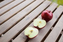 Apples whole and cut in halves on wooden surface. Close up image of one whole red apple and two halves on wooden surface outdoors Royalty Free Stock Image