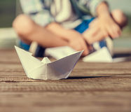 Close up image paper ship on the wooden pier Stock Photos