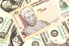 A Nigerian five naira bank note with American one dollar bills. A close up image of a peach colored, five Nigerian naira bank note on a background of American royalty free stock photos