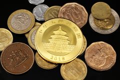 A Chinese gold coin with Chilean pesos on a black surface. A close up image of pesos from Chile with a Chinese golden coin on a black reflective surface royalty free stock photos