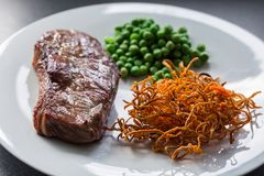 Beef steak with green peas and sweet potato stock images