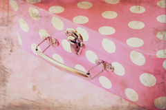 Close up image of pink suitcase with polka dots over pink background Royalty Free Stock Photography