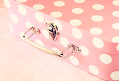 Close up image of pink suitcase with polka dots over pink background.  Stock Images