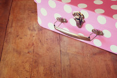 Close up image of pink suitcase with polka dots over wooden table Royalty Free Stock Images