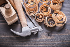 Close up image of planer claw hammer metal chisels. And wooden curled shavings on vintage wood board construction concept Stock Image