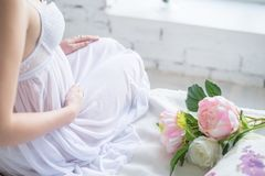 Close-up Image of pregnant woman in nice white dress touching her belly with hands and holding a bouquet of peonies. Beautiful royalty free stock photography