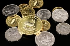 A close up image of Russian Federation coins with a gold South African Krugerrand on a black background. A close up image of a gold South African krugerrand with royalty free stock photography