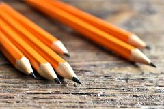Yellow Sharpened Pencils Close Up. A close up image of several wooden sharpened pencils on an old desk top Stock Photo