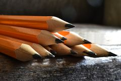 Yellow Sharpened Pencils Close Up. A close up image of several wooden sharpened pencils on an old desk top Stock Image