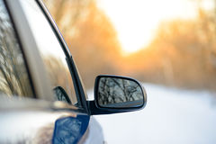 Close up Image of Side Rear-view Mirror on a Car in the Winter Landscape with Evening Sun Stock Images