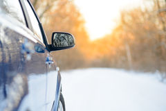 Close up Image of Side Rear-view Mirror on a Car in the Winter Landscape with Evening Sun Stock Image