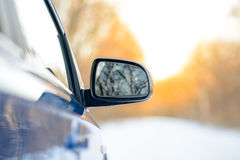 Close up Image of Side Rear-view Mirror on a Car in the Winter Landscape with Evening Sun Stock Photo
