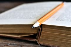 Sharpened Pencil and Old Book. A close up image of a single sharpened pencil on an old open book Royalty Free Stock Image