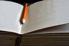Sharpened Pencil and Old Book. A close up image of a single sharpened pencil on an old open book Royalty Free Stock Photos