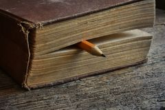 Sharpened Pencil and Old Book. A close up image of a single sharpened pencil between the pages of an old book Royalty Free Stock Images