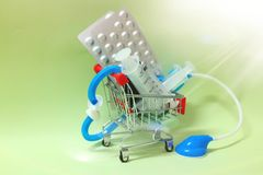 Close-up image of a small shopping cart with a syringe, medical stethoscope  Ideas, concepts, business of trading drugs. Close-up image small shopping cart royalty free stock photos