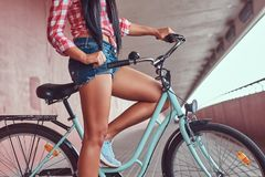 Close-up image of smooth slim female legs in blue sneakers near the city bike stock photo