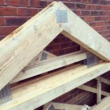 Close up image of some roof trusses stood on a building site. Prefabricated timber roof trusses stood against brick wall Stock Image