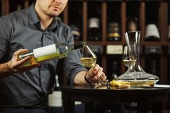 Close up image of sommelier pouring white wine from bottle in glass. Close up image of sommelier male pouring white wine from bottle having label into glass on Royalty Free Stock Photo