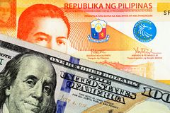 A close up image of a twenty Philippine peso with an American hundred dollar bill royalty free stock photo
