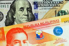 A close up image of a twenty Philippine peso with an American hundred dollar bill royalty free stock image