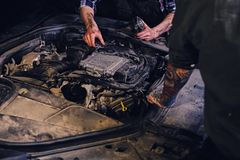 Two mechanics fixing car`s engine parts. Close up image of two mechanics with tattoos on arms, fixing car`s engine parts in a workshop Royalty Free Stock Photo