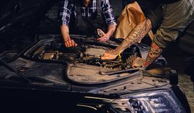 Two mechanics fixing car`s engine parts. Close up image of two mechanics with tattoos on arms, fixing car`s engine parts in a workshop Royalty Free Stock Images