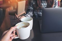Close up image of two people clink white coffee mugs while working on laptop. In cafe royalty free stock photography