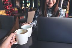 Close up image of two people clink white coffee mugs while working on laptop. In cafe stock image