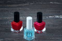 Close-up image of Two Red nail polish bottles and one colorless nail polish bottle. On grey wooden background stock photo