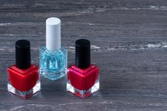 Close-up image of Two Red nail polish bottles and one colorless nail polish bottle on grey wooden background.  royalty free stock images