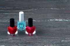 Close-up image of Two Red nail polish bottles and one colorless nail polish bottle on grey wooden background.  stock photos