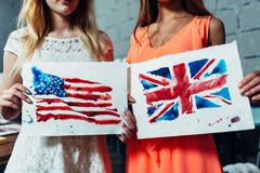 Close-up image of two young women holding a drawing of British and American flags hand-drawn with aquarelle technique on. Plain paper stock photography