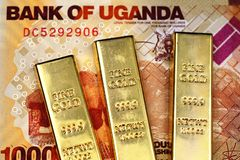 Ugandan 1000 shilling bank note with three gold bars. A close up image of a 1000 Ugandan shilling bill with three gold ingots in macro stock images