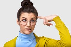 Closeup image of uncertain young woman with a bun hairstyle, bitting her lips, being doubtful, wearing casual outfit, spectacles. Closeup image of uncertain royalty free stock photography