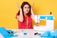Close up image of unhappy young brunette woman, sits with unpleasent facial expresions near broken sewing machine which works very. Loud, keeps hands on head royalty free stock photo