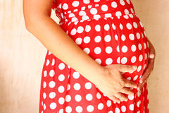 Close up image of unrecognizable pregnant woman touching her belly with her hands Stock Photos