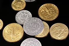 A close up image of West African Franc coins on a black background. A macro image of an assortment of West African Franc coins on a reflective black background royalty free stock images