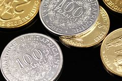 A close up image of West African Franc coins on a black background. A macro image of an assortment of West African Franc coins on a reflective black background stock photos