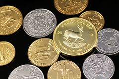 A close up image of West African Franc coins and a gold South African Krugerrand on a black background. A macro image of an assortment of West African Franc royalty free stock photography