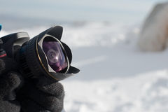 Close up image of wide angle lens on camera , snow covered landscape on the background Royalty Free Stock Image
